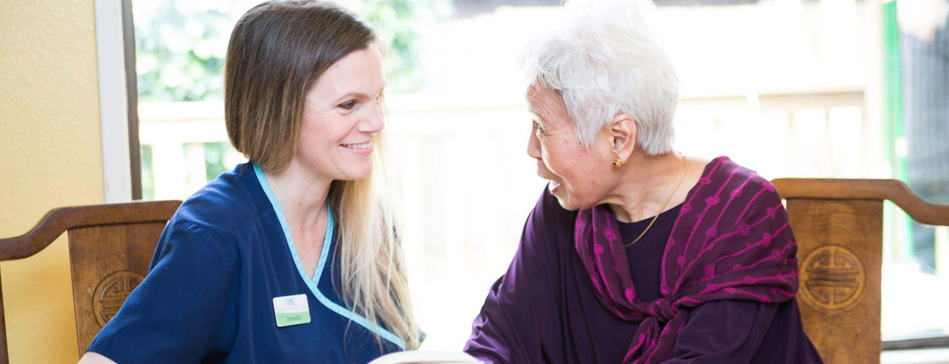 Caregiver talking with elderly woman