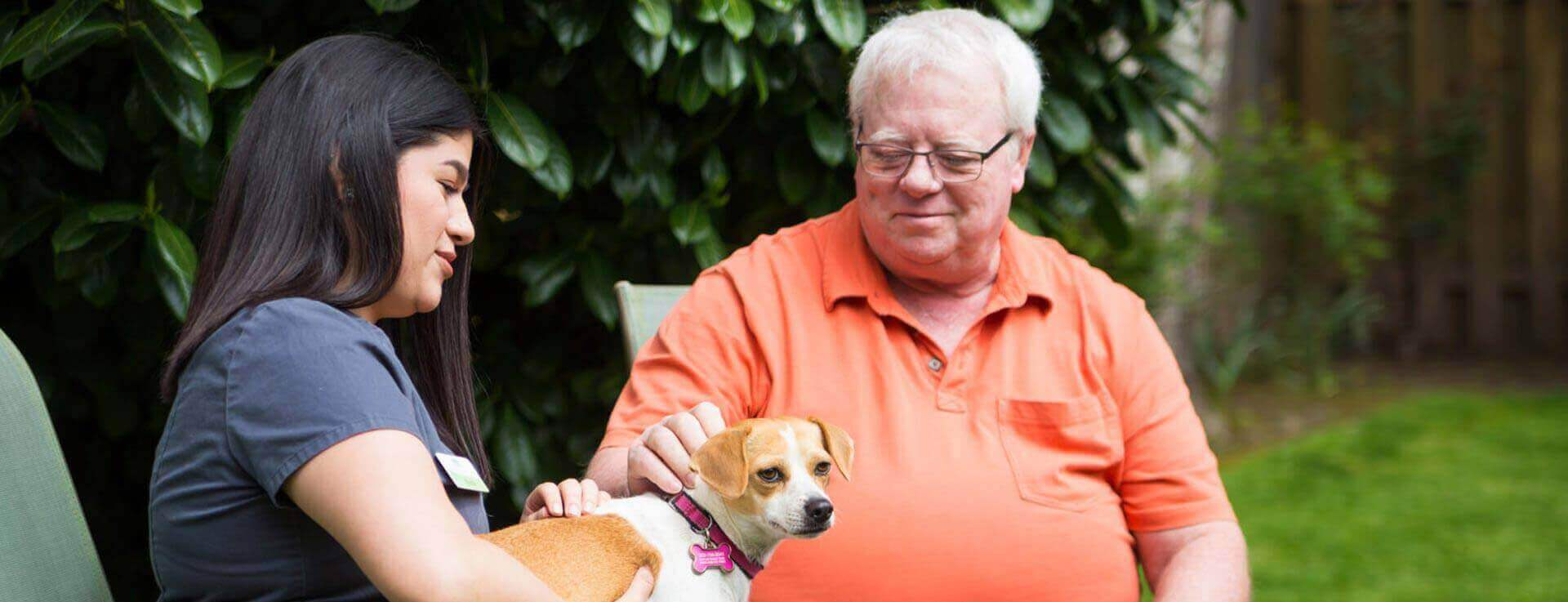 Caregiver and man sitting outside petting puppy