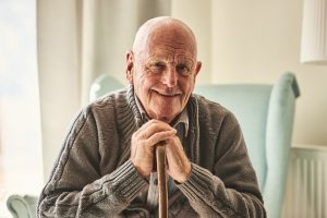 smiling senior man holding a cane